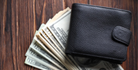 black leather wallet on top of fan of dollar bills