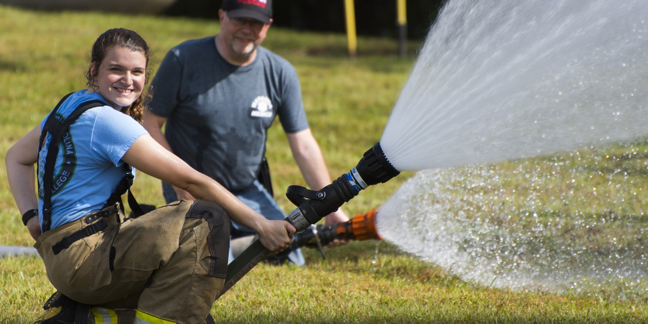 Fire students hose on ground spraying up