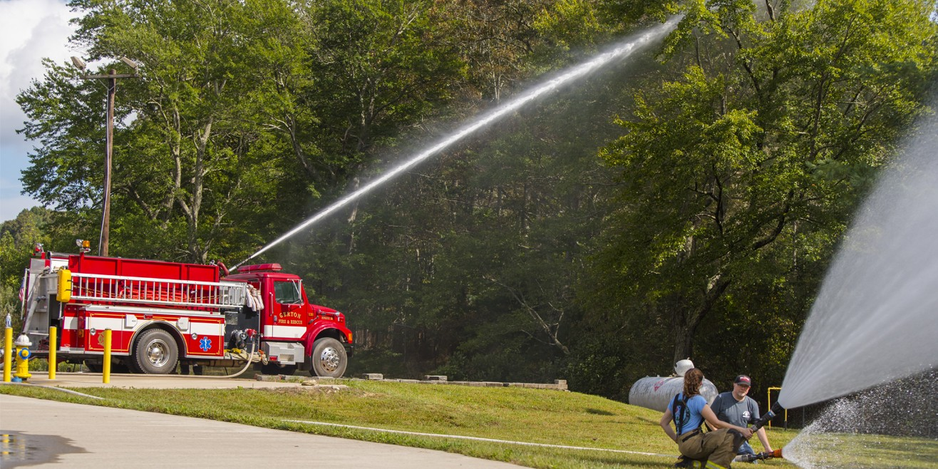 firetruck with hose spraying up high into trees