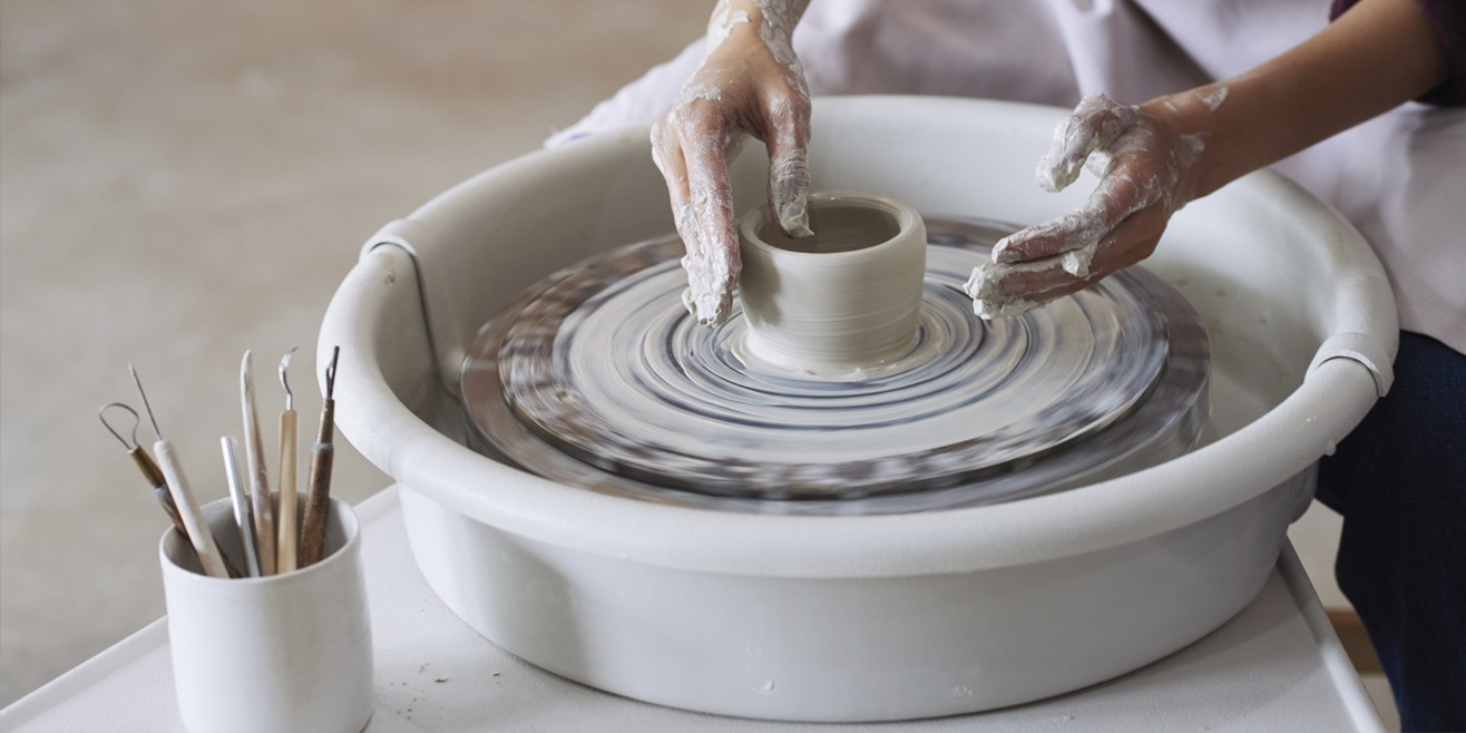 potter's hands on potter's wheels forming a pot out of clay