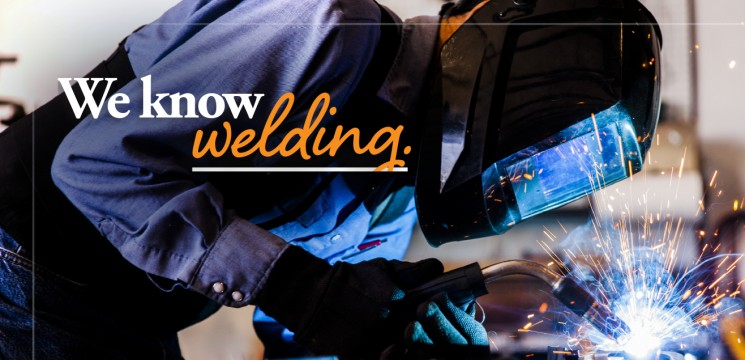 """Caption: """"We know welding."""" worker with welding torch"""