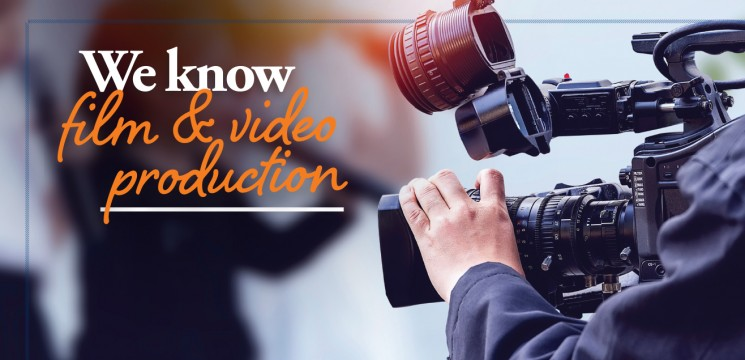 """Caption: """"We know film & video production"""" person holds film camera"""